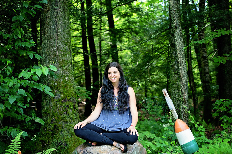 black haired woman sitting on rock in forest