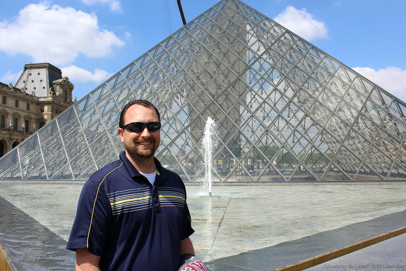 Photo of Dan enjoying some peace and quiet behind the great pyramid of the Louvre in Paris.