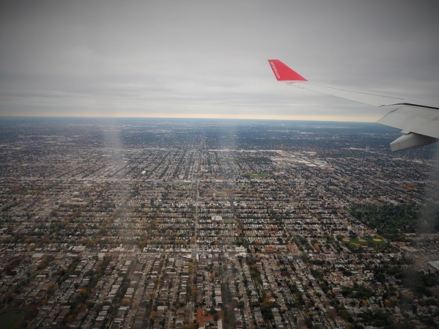 Next stop for my midlife gap year: a view from an aeroplane window of a grid of Chicago suburban housing and an aeroplane wing tip.
