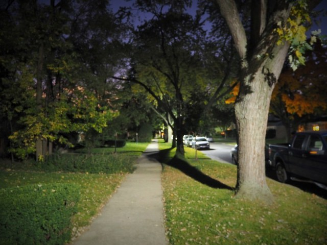 Looking up a sidewalk in American suburbia at night - trees, grass, parked cars - illuminated by street lights. The sights and sounds of my adolescence - perfect to end this day of my midlife gap year.
