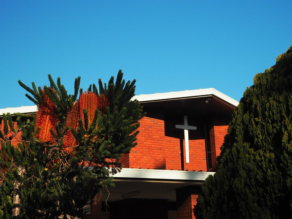 Late 1960s red brick church framed by banksia and a green bush