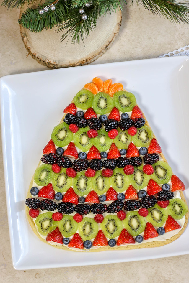 This Christmas Tree Cookie Fruit Pizza Recipe is exactly what you need this holiday season. Easy to make and serve, this #recipe is perfect for any occasion