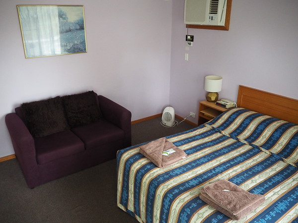 A motel room - showing a bed and love seat. Good place to sleep after riding to Gunning.