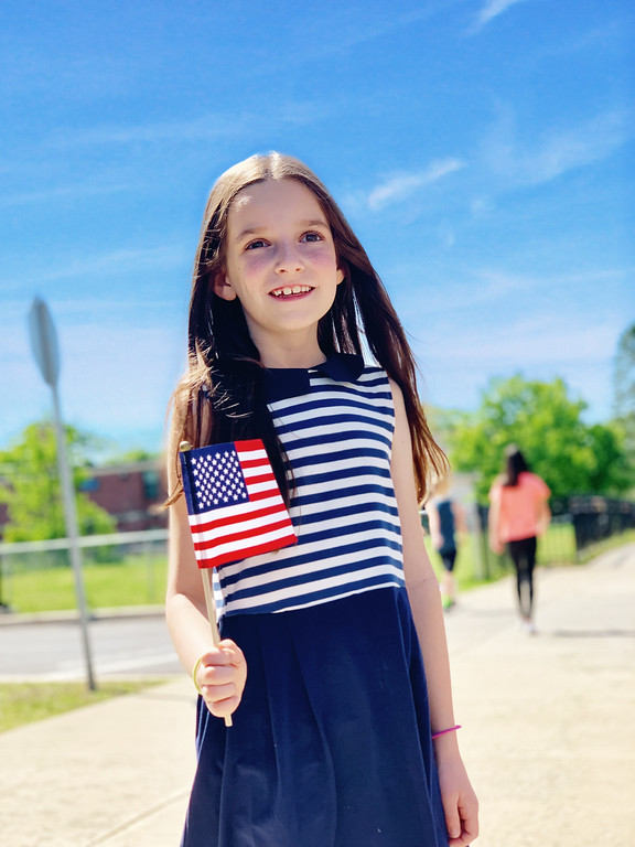 girl in striped dress holding American flag