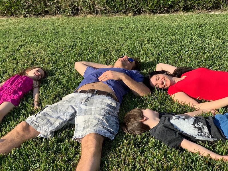 family sleeping on gras