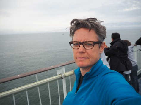 A melancholy selfie of a woman in a blue jumper on the deck of a ferry, cloudy day, dark sea, a bit of Ireland in the distance.