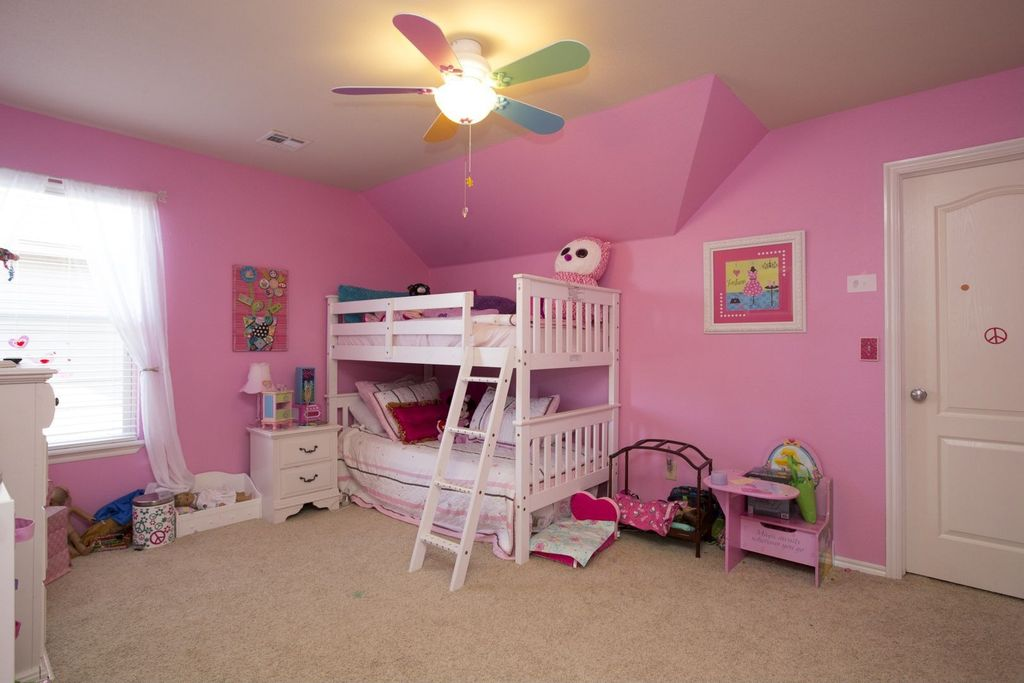traditional kids bedroom with ceiling fan & specialty door in