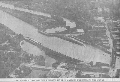 view from the air of Welland Canal at Main Street bridge, showing canal, river, aqueduct, and old swimming pools