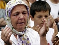 A Bosniak (Bosnian Muslim) woman from Srebrenica cries as trucks carrying 505 victims of the Srebrenica massacre pass down the main street in Sarajevo, Saturday, July 8, 2006. Trucks loaded with the coffins of the newly identified victims of Europe's worst massacre since World War II stopped for a few moments in Sarajevo on Saturday to allow hundreds of people to pay tribute to their beloved ones. The bodies will be buried at Srebrenica on the 11th anniversary of the massacre on Tuesday. (AP Photo/Hidajet Delic)(AP Photo/Hidajet Delic)