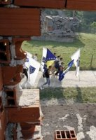 People carrying Bosnian flags pass by destroyed houses during the second day of a four-day march to Srebrenica, in the village of Liplje near Zvornik, 120 km (75 miles) north of Sarajevo, Saturday, July 8, 2006. Hundreds of Bosniaks began a four-day march on Friday along the route survivors used 11 years ago to escape the Bosnian Serb killings in Srebrenica, the worst massacre in Europe since World War II. (AP Photo/Amel Emric)