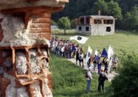 People carrying Bosnian flags pass by destroyed house during the second day of a four-day march to Srebrenica, in the village of Liplje near Zvornik, 120 km (75 miles) north of Sarajevo on Saturday, July 8, 2006. Hundreds of Bosnians began a four-day march on Friday along the route survivors used 11 years ago to escape the Bosnian Serb killings in Srebrenica, the worst massacre in Europe since World War II. (AP Photo/Amel Emric)