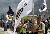 Bosnian people carrying Bosnian flags finish their four-day march to Srebrenica as they enter to the Memorial Center Potocari, near Srebrenica north of Bosnian capital Sarajevo, Monday, July 10, 2006. Hundreds of Bosnians began a four-day march on Friday along the route survivors used 11 years ago to escape the Bosnian Serb killings in Srebrenica, the worst massacre in Europe since World War II. March was a part of ceremony marking 11th anniversary of Srebrenica fall. Serb troops killed over 8,000 Bosniak men and boys at Srebrenica in 1995, and most of the bodies are still missing. (AP Photo/Amel Emric)