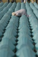 Bosnian Muslim women reacts as she finds the coffin of a relative from among 505 bodies to be buried during funeral ceremony at the Potocari Memorial Center, near Srebrenica north of Bosnian capital Sarajevo, Tuesday, July 11, 2006. The bodies will be buried marking the 11th anniversary of the massacre, when Serb troops killed over 8,000 Muslim men and boys at Srebrenica in 1995, and most of the bodies are still missing. (AP Photo/Amel Emric)