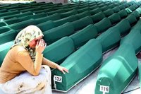 A Bosnian woman weeps next to the coffins of Srebrenica Massacre victims, Muslim men and children, before their burial in Potocari, near Srebrenica.