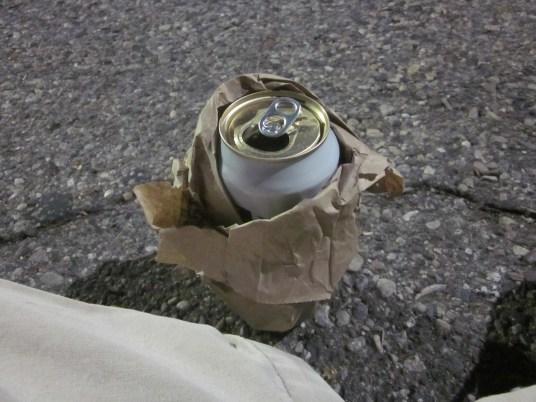 Eine Dose Bier ist in Papier eingewickelt um diese in der Öffentlichkeit aufgrund eines Alkoholverbotes trinken zu können. Detroit, USA. September 2015 // A can of beer is wrapped into paper due to a ban on alcohol in public in Detroit, USA. September 2015