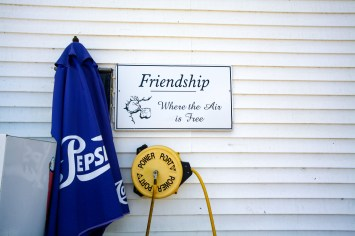",,Friendship, where the air is free"" Schild auf einem Lebensmittelgeschäft in einem Holzhaus in Friendship, Maine, USA. August 2015 // ,, Friendship, where the air is free"" sign on the facade of a small grocery store in a wooden house in Friendship, Maine, USA. August 2015"