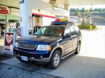 Geländewagen mit Dachträger tankt auf der Tankstelle in Britisch Kolumbien, Kanada. Oktober 2015 // SUV fills up with petrol at a gas station in British Columbia, Canada. October 2015.