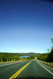 Endlos erscheinender Trans Canda Highway one führt durch einen Wald und an einem See vorbei. Kanada. Oktober 2015 // Endless appearing Trans Canada Highway one leads through a forest and a lake. Canada. October 2015