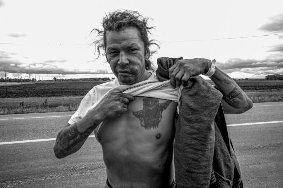 Ein native american Autostopper präsentiert am Trans Canada Highway seine Tätowierungen. Saskatchewan, Kanada. Oktober 2015 // A native american hitch-hiker presents his tattoos at the Trans Canada Highway One. Saskatchewan, Canada. October 2015