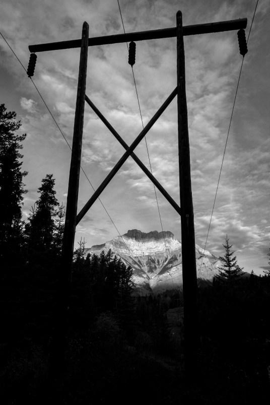 Hölzener Strommast vor dem Hintergrund eines Berges trägt Stromkabel mitten durch den National Park Banff in in Kanada, Alberta. Oktober 2015 //Wooden pylon is carrying power cables in the middle of National Park in front of a peak in Banff in Canada, Alberta. October 2015