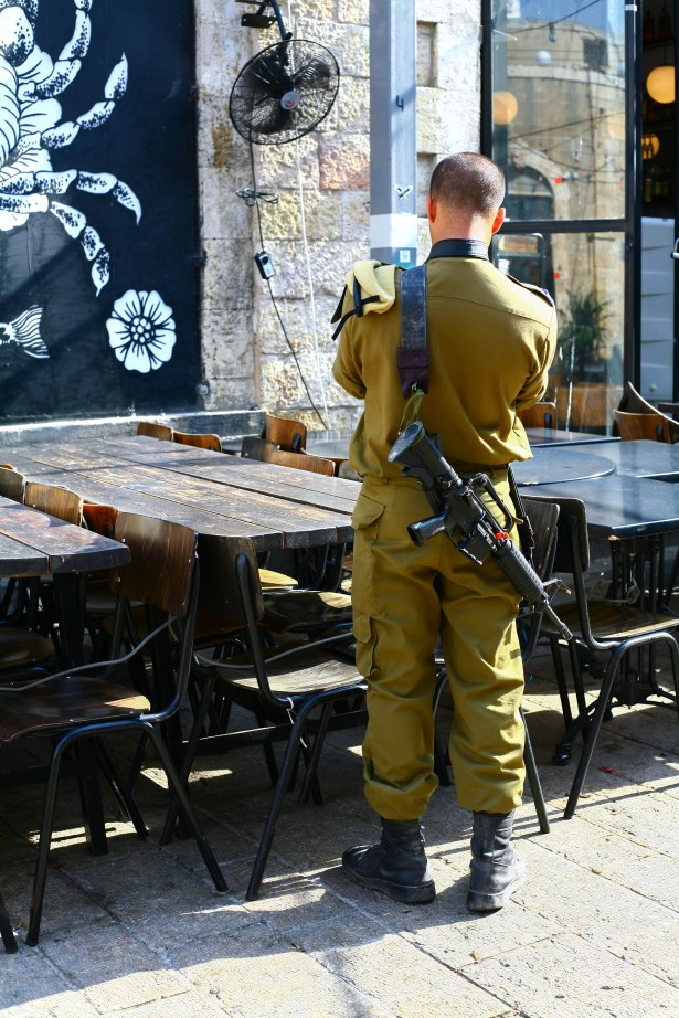 Ein Soldat trägt ein Gewehr am Rücken in Tel Aviv, Israel. Juli 2017 // Soldier is having a rifle on his back in Tel Aviv, Israel. July 2017