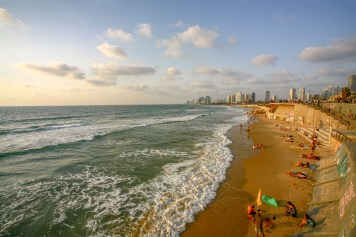 Blick auf den Strand und die Skyline von Tel Aviv in der Abendsonne. Tel Aviv, Israel. Juli 2017 // View on the beach and skyline of Tel Aviv in the evening sun. Tel Aviv, Israel. July 2017