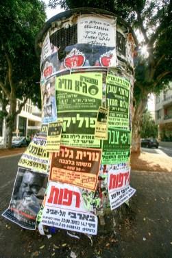 Litfaßsäule mit vielen Werbeplaketen in Fußgängerzone in Tel Aviv, Israel. Juli 2017 //Advertising pillar with lots of posters in the pedastrian zone in Tel Aviv, Israel. July 2017
