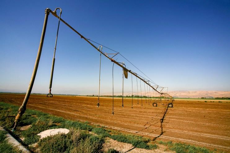Großes Feld wird von einer Dürreperiode geplagt und muss mit einer Bewässerungsmaschine versorgt werden. Israel, Juli 2017 // Field needs to get irrigated with a special construction due to a long period of drought in Israel, July 2017