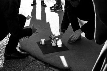 Ein Gruppe Kleinkriminieller entlocken Torusiten Geld mit dem alt bekannten Hütchenspiel in Paris, Frankreich. Dezember 2016 // A group of small time criminals enticing tourists to play a game for money Paris, France. December 2016.