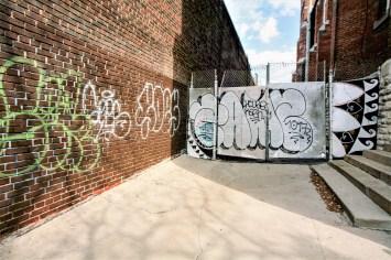 Mit einem Graffiti besprühte Mauer sowie einem Tor, das mit einem Stacheldraht versehen ist in Toronto, Kanada. Mai 2015 // Graffiti paintings and Tags on a wall and a gate which has an barbed wire on it in Toronto, Canada. Mai 2015
