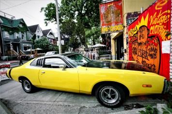"Gelb-schwarz lackierter amerikanischer Wagen vor Geschäft ,,King of Kensington"" in Toronto, Kanda. Mai 2015 // Yellow-black varnished US muscle car in front of the ,,King of Kensington"" shop in Toronto, Canada. May 2015"