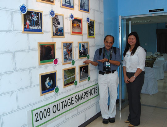 Prof. Joey Tañedo, FPPF mentor, poses with Lyra Guinto, a lady manager at the Quezon power plant before the wall of winning photographs from the company's 2009 Outage Snapshots contest.