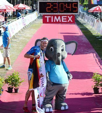 """Raelert with """"Laguna"""" official LPT mascot at the finish line."""