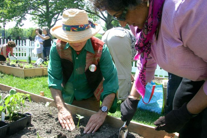 Volunteers are taking advantage of the nice day in May to plant herbs, vegetables, and flowers.