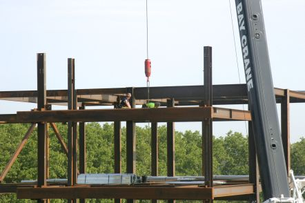 Beams are lifted by a very large crane as workers are building the third level.