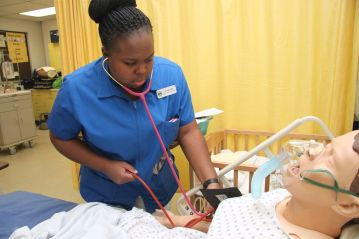 A nursing student measures the blood pressure of the mock patient.