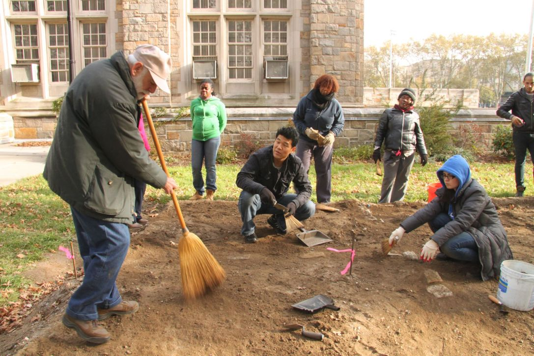 Professor Louis Flam shows students how to remove dirt carefully on an evacuation site.