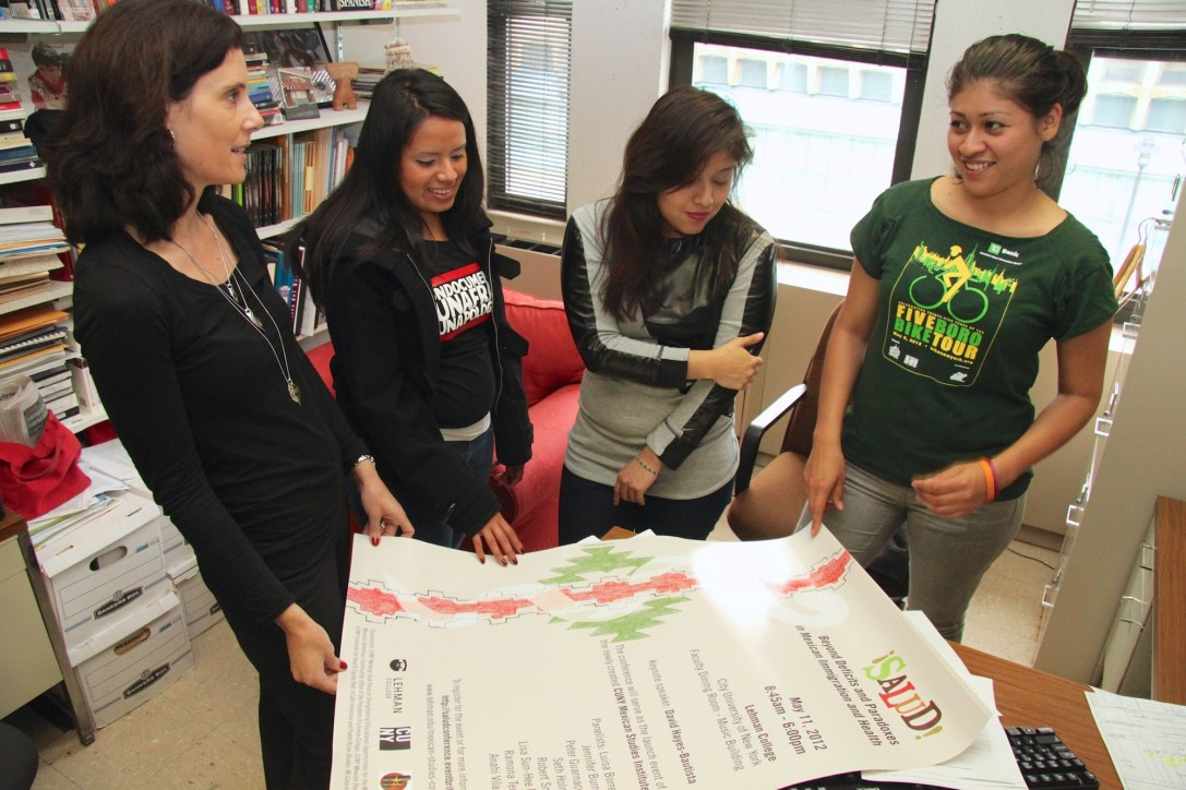 Professor Alyshia Gálvez (far left) shows the annual conference poster to students (from left to right) Marlen Fernandez, Rosario Cecilio Flores and Karen Rojas.