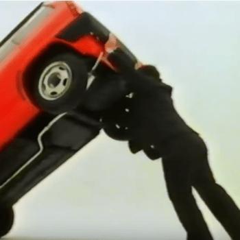 Screenshot of Geoff Capes lifting a car overhead
