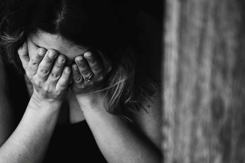 black and white photo of a woman holding her face in her hands