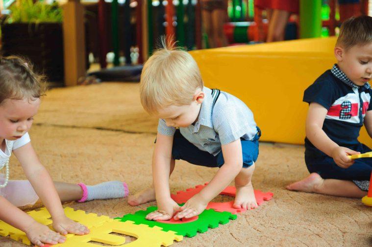 All'asilo nido 3 bambini giocano al parcogiochi