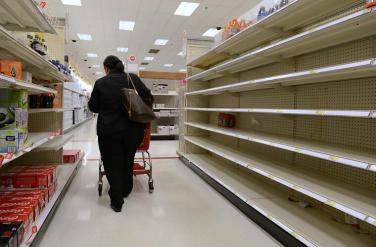 epa03451648 A shopper walks past mostly empty shelves in the beverage section of a grocery store that was depleted ahead of Hurricane Sandy, in Alexandria, Virginia, USA, 29 October 2012. US President Barack Obama urged residents to follow warnings from local officials as hurricane Sandy barrels toward the East Coast. Many areas from the mid-Atlantic to Northeast have declared a state of emergency as Sandy is expected to bring flooding and widespread power and commuication outages. EPA/MICHAEL REYNOLDS