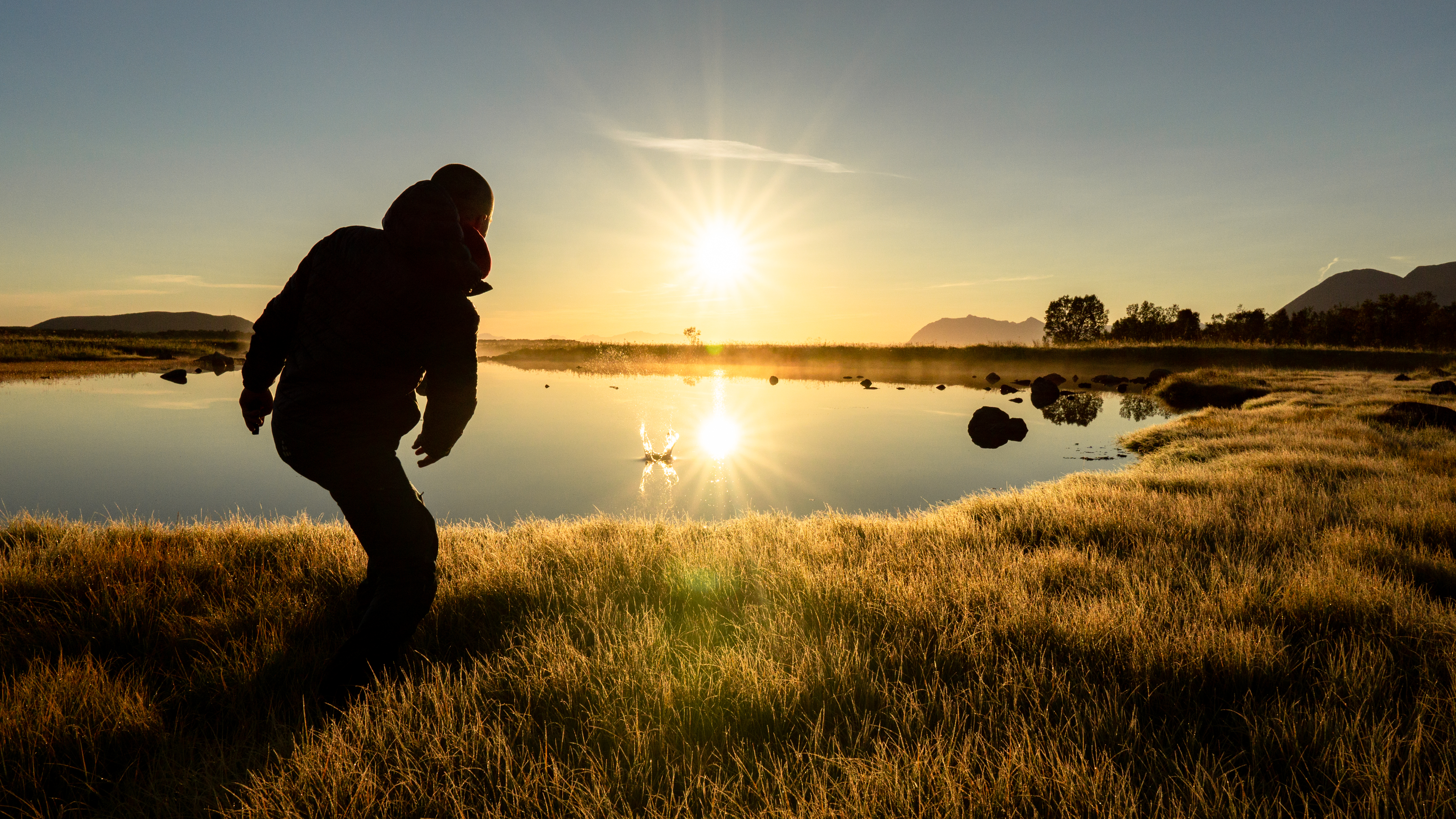 Download Man Throwing a Stone into a Calm Lake During Beautiful Sunrise FREE Stock Photo