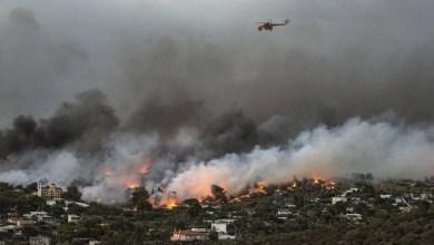 Un elicottero porta acqua sulla cittadina di Rafina, Grecia, 23 luglio 2018 (ANGELOS TZORTZINIS/AFP/Getty Images)