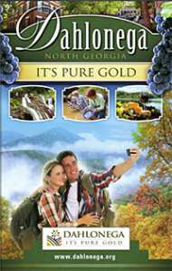 The front page of the dahlonega visitors guide. Features a couple taking a selfie on top of the mountains, and children digging for gold.