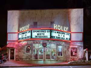 The outside of the historic holly theatre, located in Dahlonega. Shows are advertised on the billboards located in the front, with the words 'holly' lit up in bright yellow theatre lighting