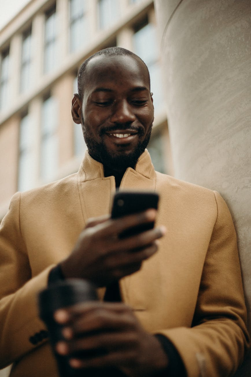 smiling man looking at his phone leaning on concrete pillar