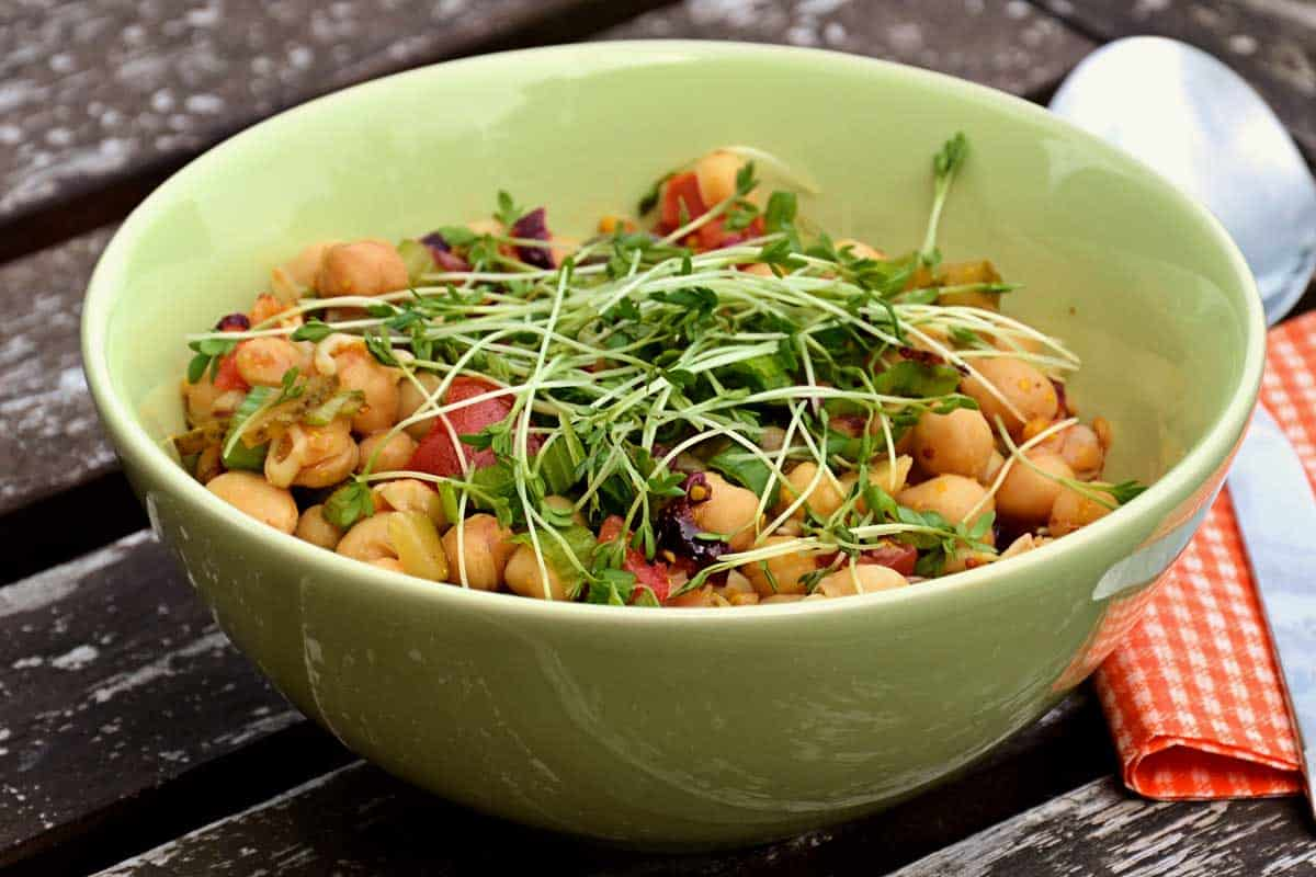 Green bowl with chickpea salad on a picnic table.