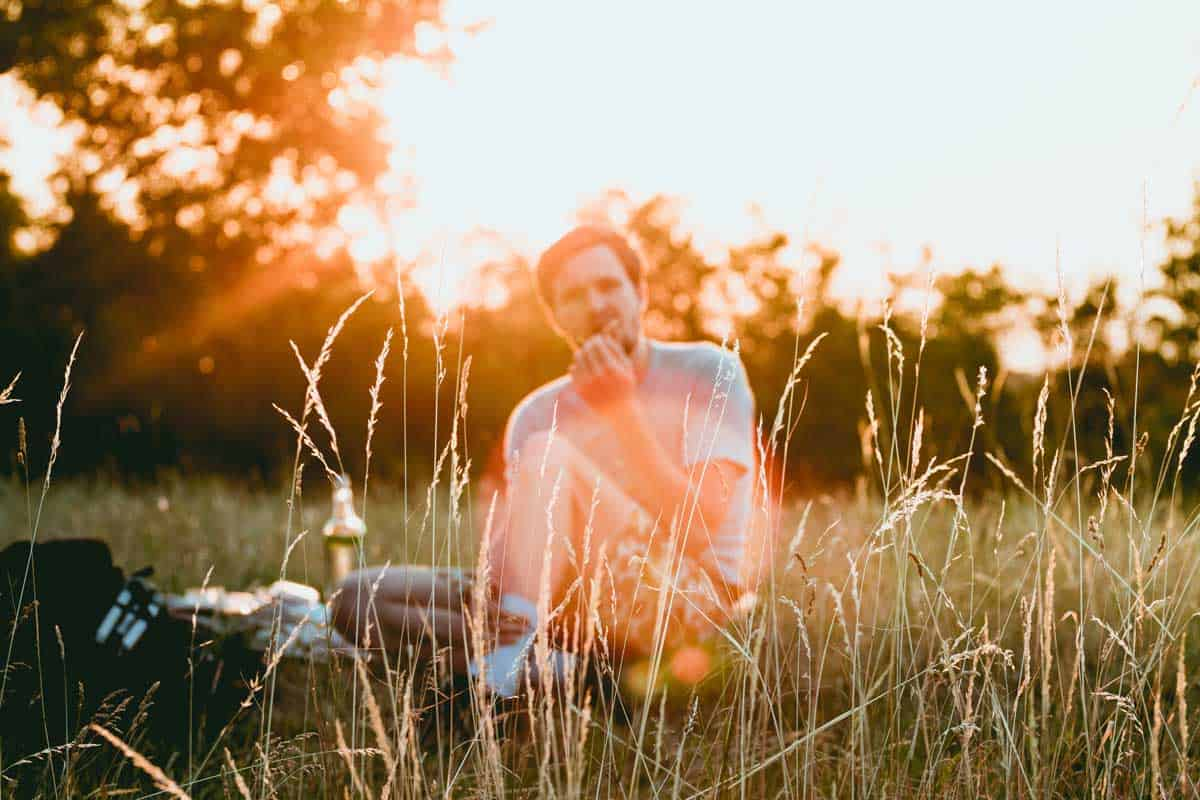 Man sitting in a field having a picnic with sun in the background.