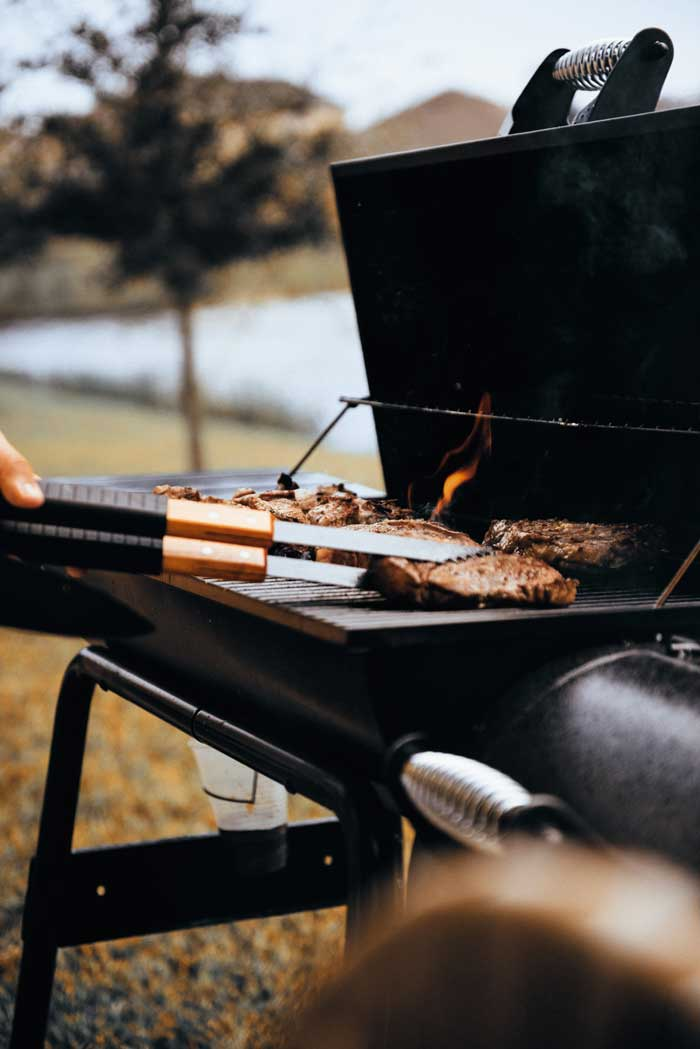 Close up of steaks on a gas BBQ.